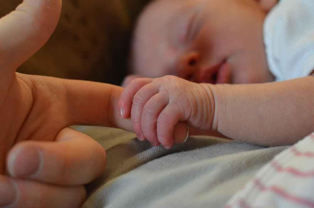 baby holding human finger