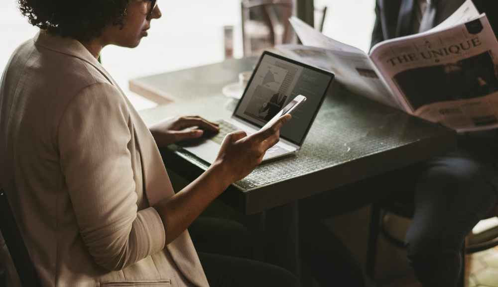 woman using smartphone and laptop near black table